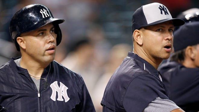An injured New York Yankees' Alex Rodriguez, right, talks with Carlos Beltran, left, prior to a baseball game against the Arizona Diamondbacks Monday, May 16, 2016, in Phoenix.