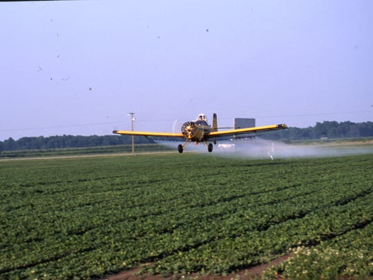 A crop duster sprays a field with fertilizer in Sussex