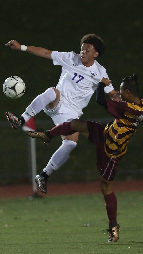 From left, New Rochelle's David Lopez (17) kicks the