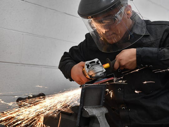 Gerardo Garcia uses a grinder in a welding class at