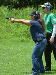 Jackie Follin of Naples takes aim as instructor Shirley Watral looks on. The Altair Gun Club held a Pistol 1 training course specifically for women on Saturday, July 16 at their shooting facility in Copeland.