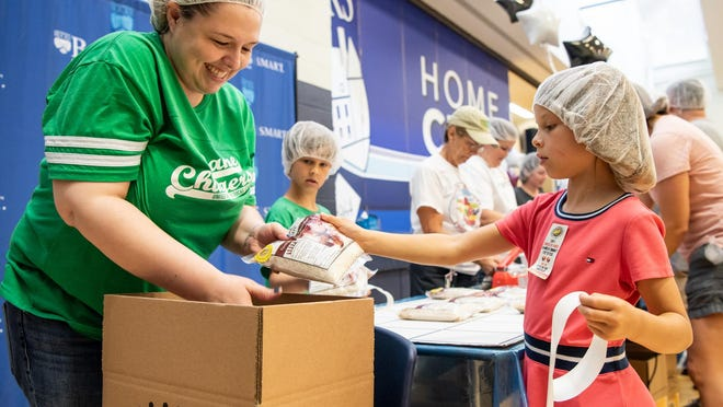 Faith Parkinson, left, director of finance at the United Way of Bucks County, and Charlotte Strouse, 7, of Middletown, stickers and pack meals with Charlotte's brother, Walter Strouse, 8, during the 2019 Bucks Knocks Out Hunger event. The popular food-packing event will not take place this year, but there are still ways you can help.