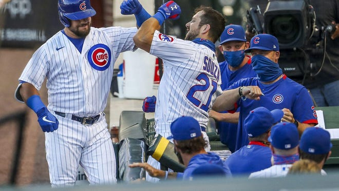 Chicago Cubs left fielder Kyle Schwarber, left, celebrates with right fielder Steven Souza Jr. (21) after Schwarber hit a solo home run during the second inning against the Milwaukee Brewers at Wrigley Field on Thursday, Aug. 13, 2020.
