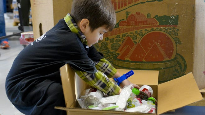 Maverick Ortiz, 4, removes Pringles from boxes at America's Second Harvest of Coastal Georgia on Monday during the United Way Volunteer's service event. Georgia Power sent employee volunteers to the event, which included Maverick's dad, Matt Ortiz.