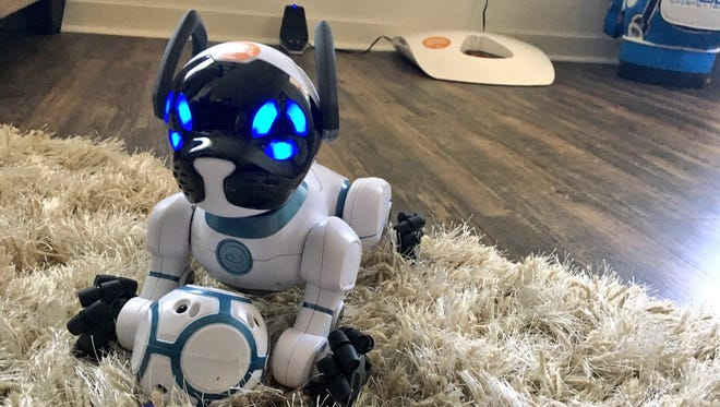 """""""Chip"""" the robotic dog plays while visitors tour the Cox """"smart home"""" on April 13, 2017."""