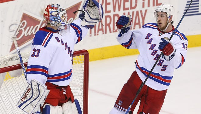 New York Rangers right wing Kevin Hayes (13) congratulates New York Rangers goalie Cam Talbot (33) after their 4-2 win over the New Jersey Devils at Prudential Center.