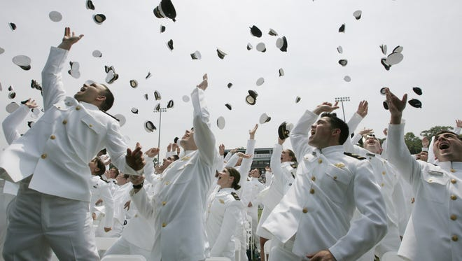 Graduates toss their hats into the air after graduating from the U.S. Merchant Marine Academy in Kings Poiint, N.Y., Monday June 19, 2006.