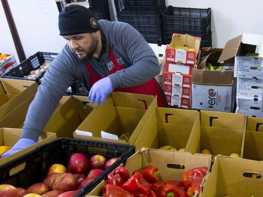 """Imperfect Produce operation associate, Brutus Oliverira, assembles boxes of """"ugly"""" fruits and vegetables."""