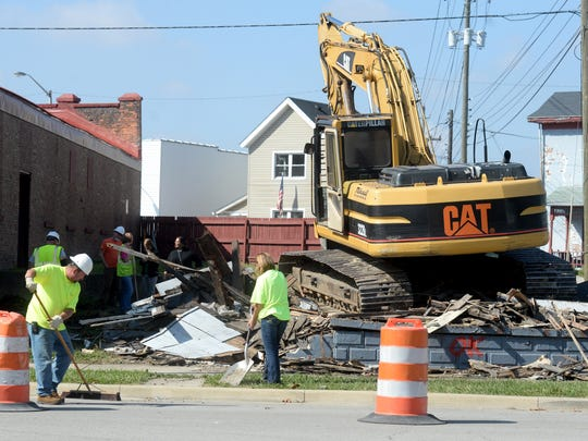 A crew sweeps up debris after tearing down a house