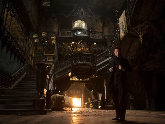 Tom Hiddleston stands in the grand entry of 'Crimson