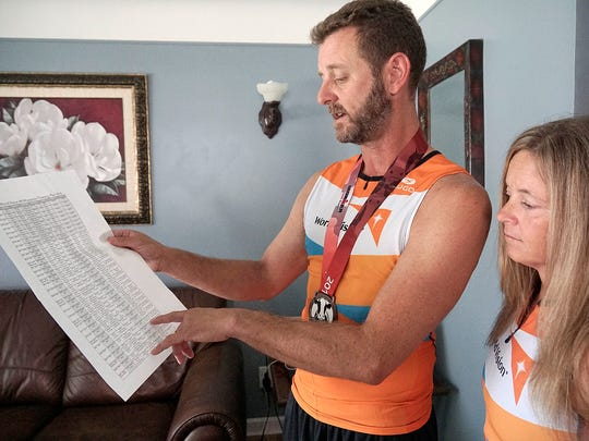 Matt and Hollie Thompson look at their training schedule they followed to prepare for the Ironman competition.