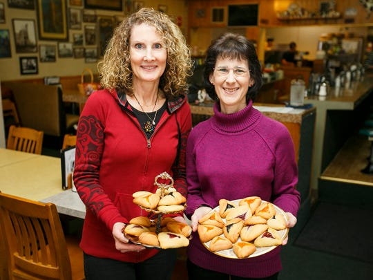 Stacey Brown, left, and Sherry Dunning show off a platter of hamantaschen, a traditional three-sided filled cookie made for Purim, the Jewish festival honoring Queen Esther.