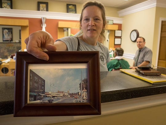 Larry Moraca's barber shop on Forest Street is decorated with scenes of old Plymouth. Ellen Elliott shows one of Moraca's  framed post cards.