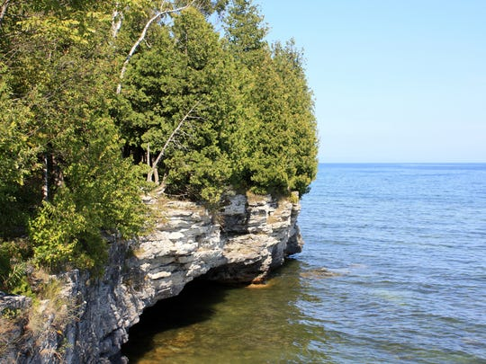 White, blocky cliffs that are part of the Niagara Escarpment line the Lake Michigan shoreline at Cave Point County Park in Door County.