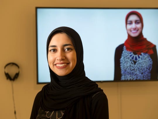 "Muslim Feminists for the Arts Co-Founder Sarah Attalla MGSA '19 stands in front of art gallery exhibit titled ""Stories of Muslim Women at Rutgers."""