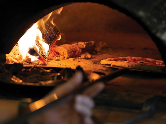 Pizza baking in wood oven