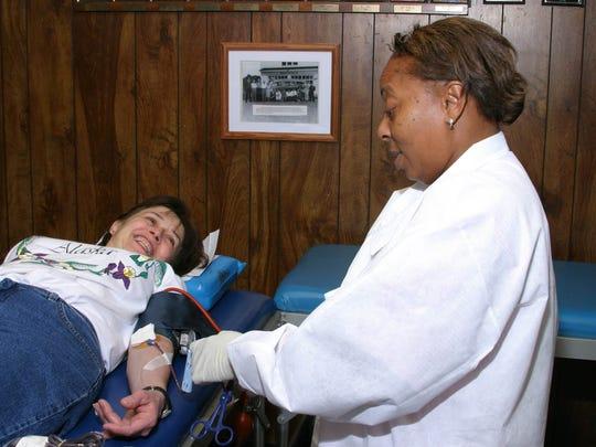 Nurse Michelle Elder assistsdonor Elise Boschen at Jim Gilligan's monthly blood drive in April  2004.