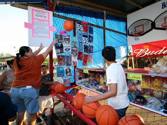 In this file photo, Ramona Taitingfong, 21, tries her luck at the Basketball Throw booth at the Liberation Carnival.