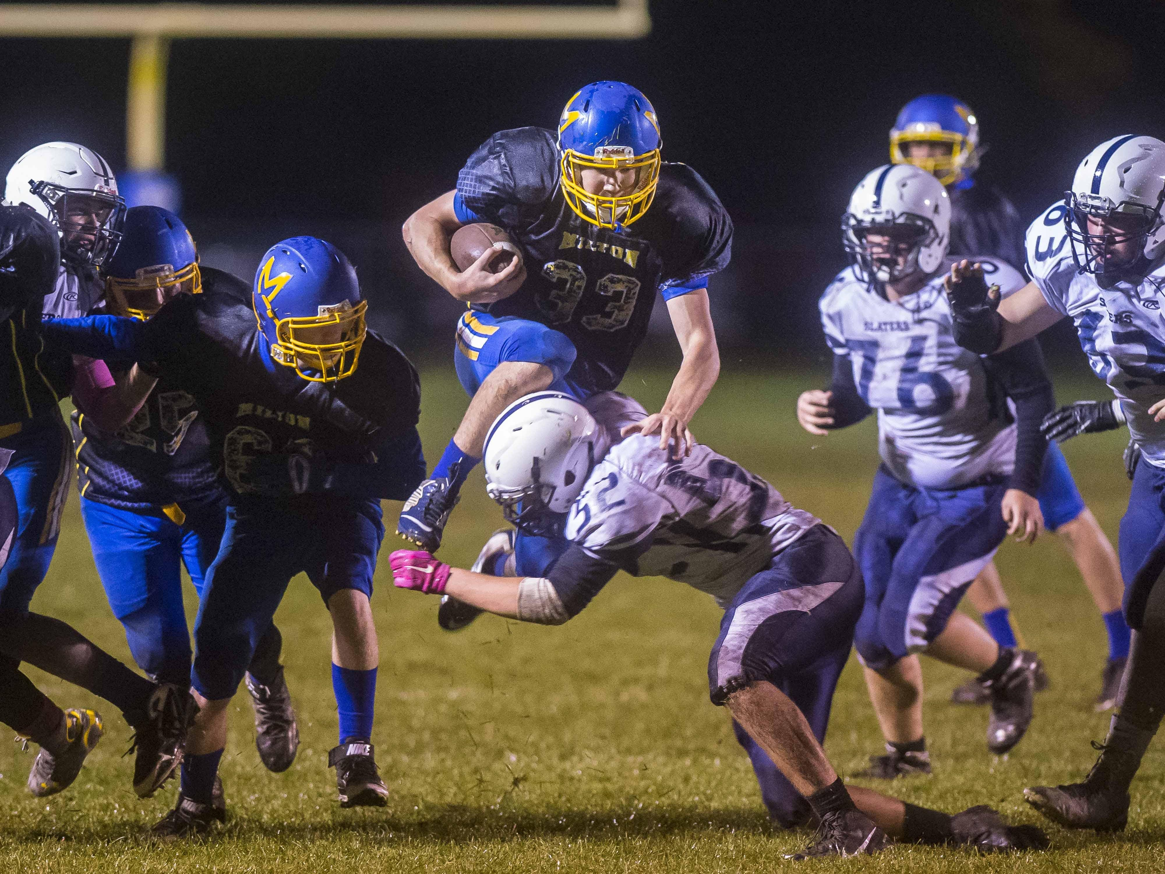 Milton's Ian Kandzior leaps over Fair Haven's Jake Stoodley during Friday night's game in Milton. The Yellowjackets won 38-20.