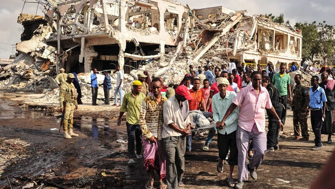 Somali men carry the body of a victim who died in the explosion of a truck bomb in the centre of Mogadishu, on October 15, 2017.