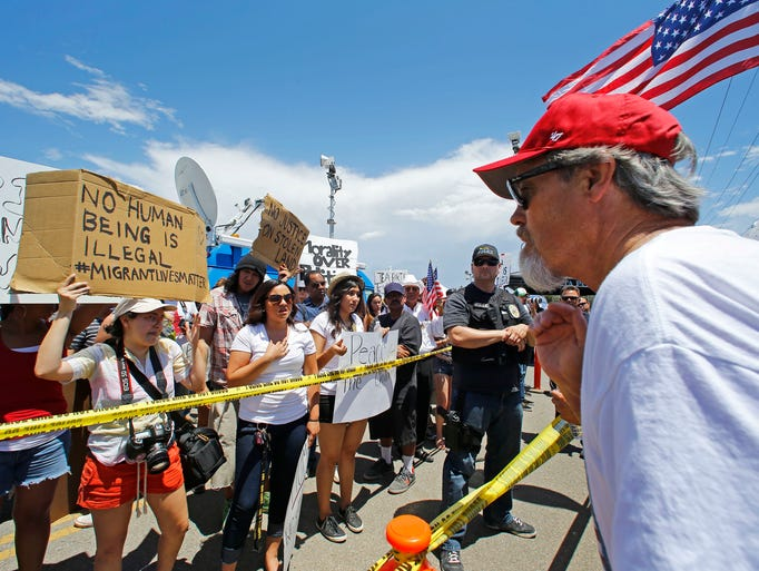 People form both sides of the issue argue across police lines during a immigration demonstration outside the border patrol facility on July 4, 2014 in Murrieta, Calif.