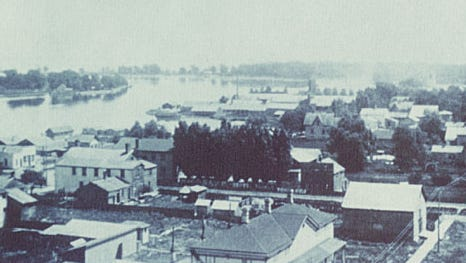 This 1889 aerial photo shows the city of Neenah, facing east from the City Hall tower. The Fox River can be seen on the left.