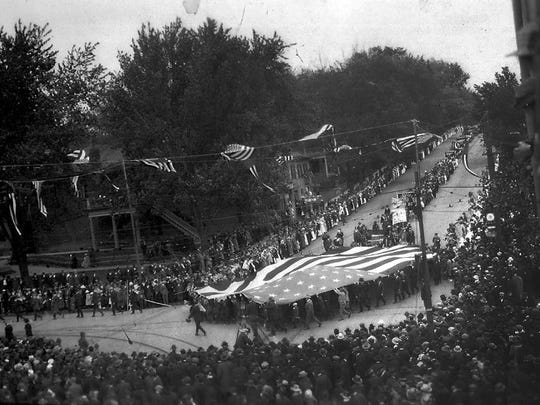 The gigantic flag made by the women of Lancaster's Elks Lodge No. 570 in 1916 is shown being carried in a parade on Main Street hill. The date of the photo is not known.