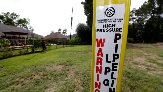 A pipeline marker stands near homes  in Port Arthur, Texas.