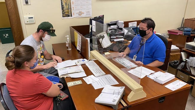 Deputy Pueblo County Clerk Michael Boydstun, right, helps two Pueblo County citizens at the clerk's office Wednesday. Citizens need to make an appointment and late fees from March through June have been waived.