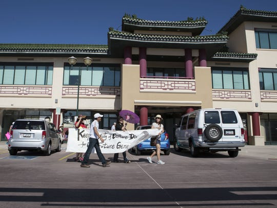 Protesters walk through the Chinese Cultural Center