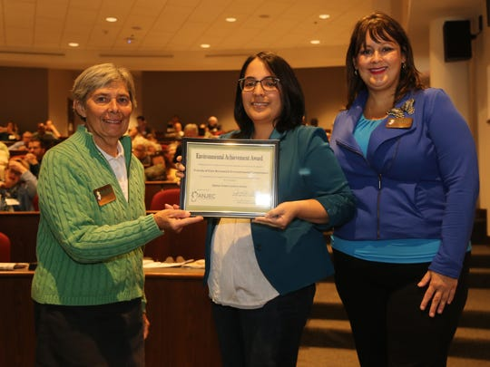 Association of New Jersey Environmental Commissions President Nancy Tindall and Executive Jennifer M. Coffey present East Brunswick Public Library Programming Librarian Melissa Hozik with the Environmental Achievement Award for the Friends of the East Brunswick Environmental Commission and East Brunswick Public Library's Option Green programming series.