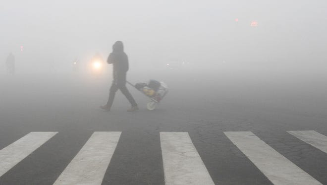 A pedestrian crosses a smog-shrouded street in Lianyungang, eastern China's Jiangsu province on December 19, 2016.