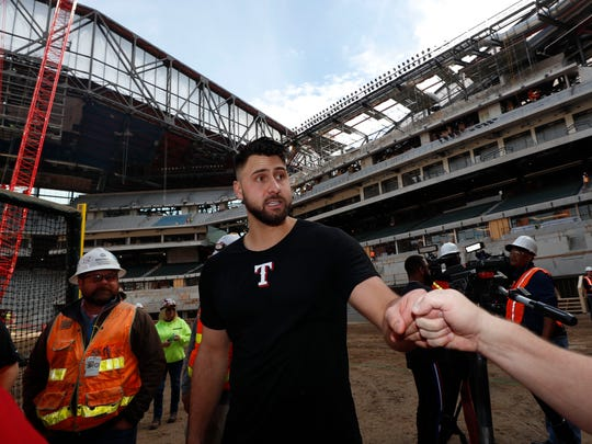 FILE - In this Dec. 4, 2019, file photo, Texas Rangers' Joey Gallo is greeted after a batting practice at the under construction baseball field at the new Rangers ballpark in Arlington, Texas. Joey Gallo likes what is being built for inside the new ballpark that will have a retractable roof.  (AP Photo/LM Otero, File)