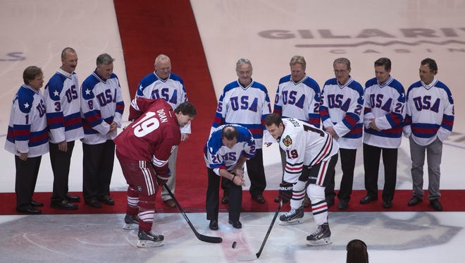 Mike Eruzione (center), captain of the 1980 Olympic USA gold medal hockey team, drops the puck with his 1980 teammates before the game at then-Jobing.com Arena in Glendale on Feb. 7, 2014.