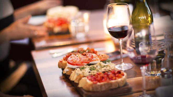 Postino Wine Cafe's bruschetta paired with a glass of wine is a perfect happy hour treat.