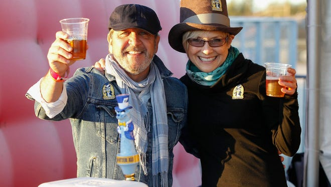 Marc Paulhus and Lynette Koftinow of Mad Otter Ale (Monterey, CA) are photographed holding one of the company's brews being offered during the inaugural Blues & Brews at Mazda Raceway Laguna Seca Marketplace on Saturday, October 21. 2017 in Salinas, Calif.