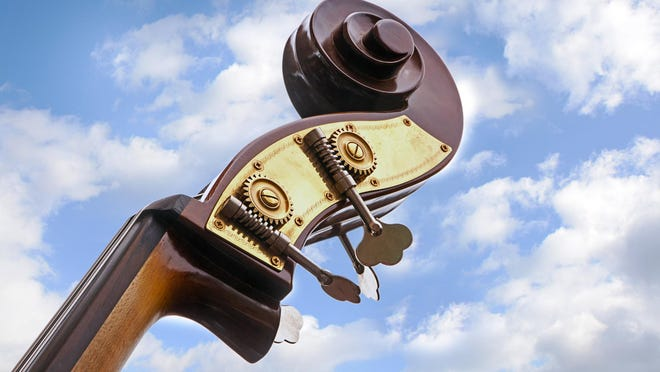 double bass, detail of the music instrument neck, head with tuning pegs and scroll against a blue sky with clouds, view from below, copy space