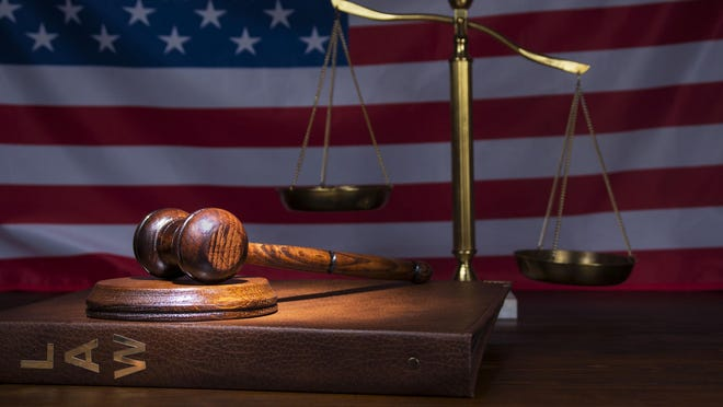 Scales of Justice with gavel and American flag in the backround