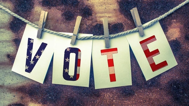 The word VOTE stamped on card stock hanging from old twine and clothes pins.