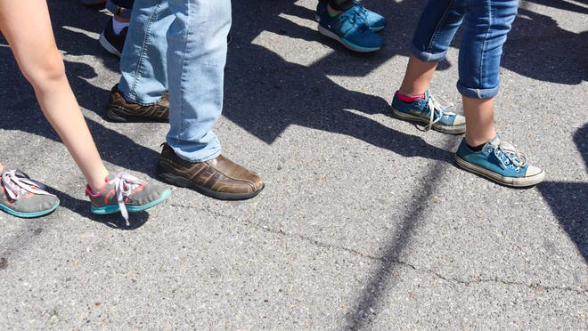 Closeup of feet and legs - People walking on cracked sidewalk with various shoes and pants