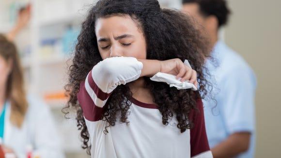 Mixed race preteen girl sneezes into her arm