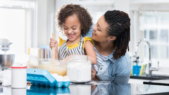 African American mom and daughter bake cake together