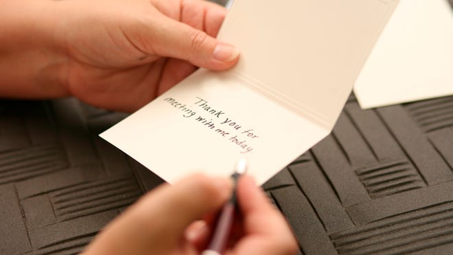 Female hands writing a thank you note.