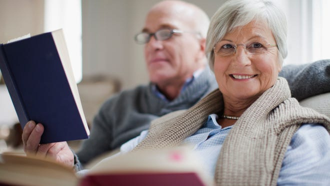 Senior couple smiling and reading books