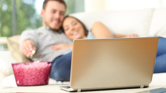A young couple cuddle on the couch with a bowl of popcorn and a laptop.