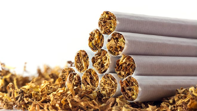 A pyramid of cigarettes sitting atop a bed of dried tobacco.