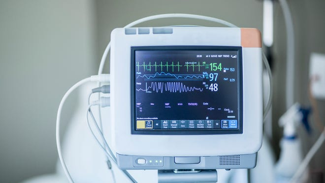 Medical monitoring equipment, with a hospital bed in the background.