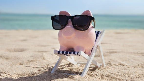 Piggy bank on the beach wearing sunglasses.