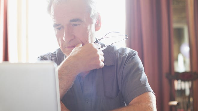 Older man at laptop with eyeglasses in hand