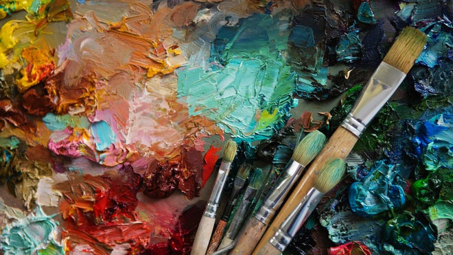 A closeup view of a painting with paintbrushes lying on it